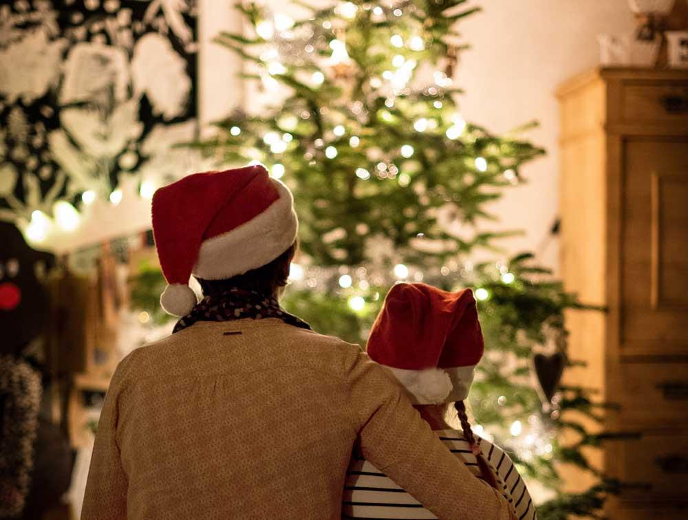 Mutter mit hochsensiblem Kind vor dem Weihnachtsbaum